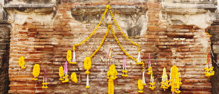 lei: Flower lei hanging on the brick wall to worship in buddhist offering to god
