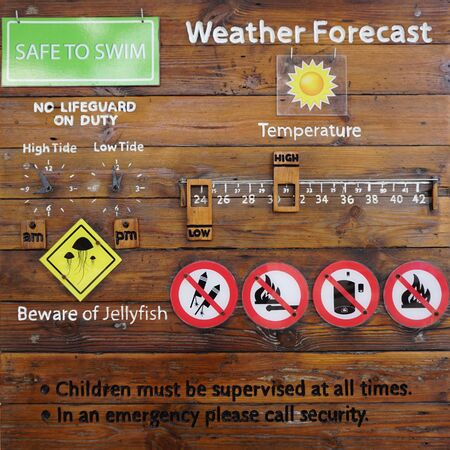 signage outdoor: Beach safety signage written on the rustic timber plank board