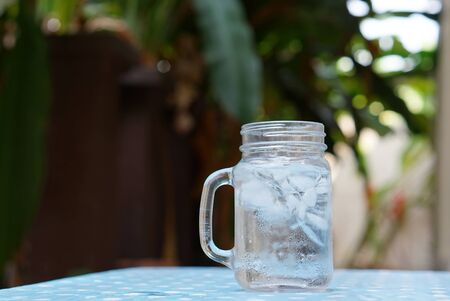 glass jar: Ice water in the glass jar with nature background Stock Photo