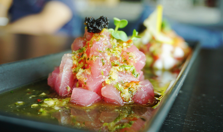spicy raw tuna with chopstick on the black plate