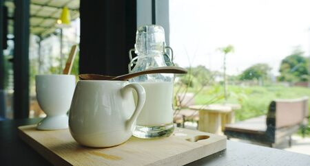 ceramic bottle: White ceramic cup with milk bottle on timber block