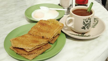 Asian breakfast contain of toasted bread ,soft boiled egg and hot coffee 版權商用圖片