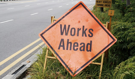 work ahead: Work ahead signage along the street with plants background Stock Photo