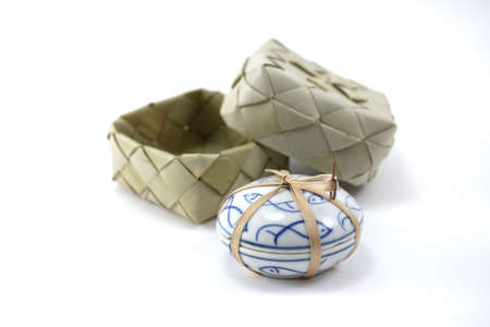 string together: isolate image of small ceramic Asian fish pattern round shape container tight together with bamboo string with woven box background