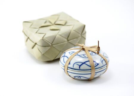 string together: isolated of small ceramic round shape container tight together with bamboo string with woven box background isolated