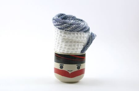 tumbler: white towel rolled with blue egde put inside the face painted cup with white background