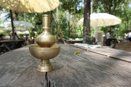 pinchbeck: Buddist water vase made from brass on the rustic timber table with nature background