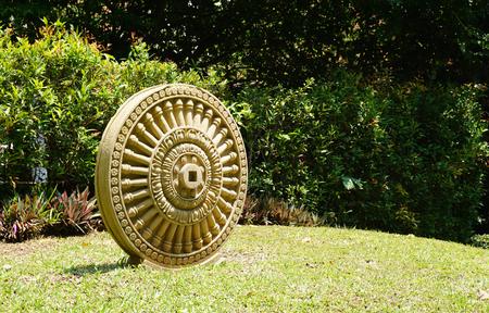dhamma: dettaglio elevazione della pietra arenaria craving Dhamma ruota sul prato con impianto di sfondo sotto la luce del sole