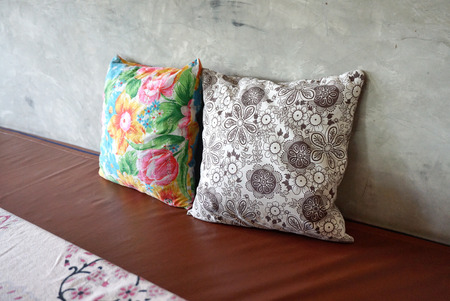 throw cushion: Colorful 2 pieces of flower pattern throw cushion on brown seating and concrete wall background