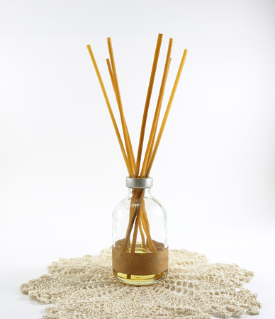air diffuser: aroma diffuser sticks in glass bottle on Crochet mat on white background