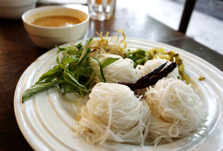 closed op detail of Asian rice noodle with vegetable eating with curry crab sauce on white plates Stock Photo