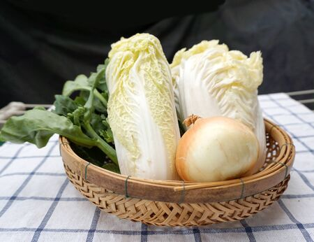 checker board: closed up of fresh vegetables  onion lettuce on the checker board facric