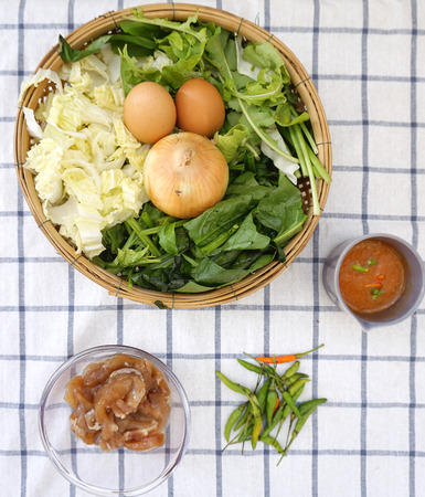checker board: top view of Food ingredients for Thai style vegetable soup with chicken on the checker board fabric