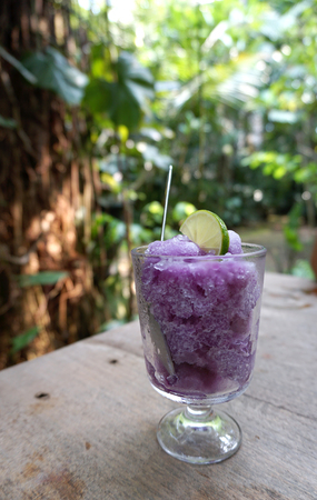potation: purple color pea flowers frappe ice cream in clear glass with lemon slide on top Stock Photo