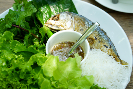 closed up: closed up of Thai style fried mackerel fish serving with fresh salad , rice noodle and spicy dressing sauce