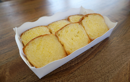 suger: bread and butter toast in the paper box on timber table Stock Photo