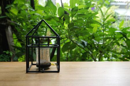 candle holder: black frame Candle holder in house shape onthe timber table with nature background