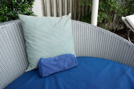 white backing: Blue and white stripe cushion on blue beach bed with grey plastic woven backing