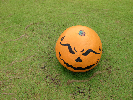 ghost rock: Evil face on orange round shape rock  with green grass background