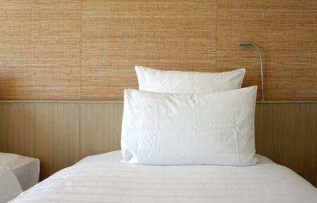 Dubbele witte kussen op wit beddoek met houten backing en behang achtergrond
