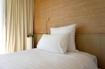white backing: Double white pillow on white bed sheet with timber backing and wallpaper background