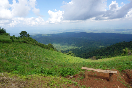 timber bench seat: Wooden bench on the hills with green mountain background