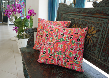 throw cushion: Generic colorful tribe pattern pillow on vintage bench