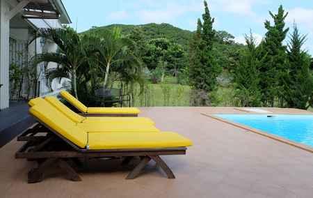 recliner: Yellow outdoor recliner chair next to the pool with mountain background