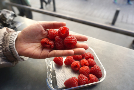 'pick up': raspberry in the plastic box with human hand pick up on the table