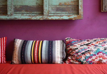 throw cushion: Cozy colorful pattern throw cushion on the red seat