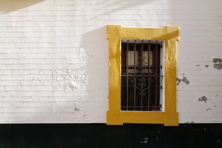 cracked concrete frame: Yellow paint window frame on the white wall at the old town of Sevilla with morning light