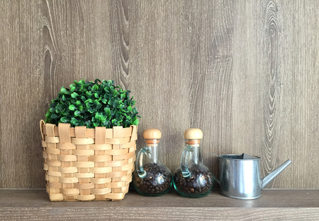double glass: Double glass jar with coffee bean inside and fake plants and small water can with timber background