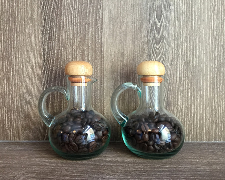 double glass: Double glass jar with coffee bean inside with timber background