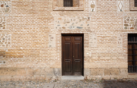 toledo town: Vintage european style timber door with brick wall background at old town of Toledo