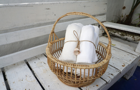 tight: Rolls of white color towel tight together by linen string with sea shell in the woven basket