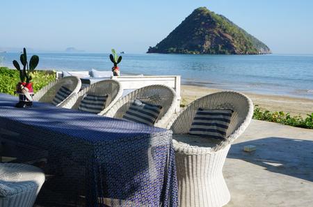 wickerwork: wickerwork chair on the beach with island background Stock Photo