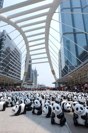 wwf: Bangkok, Thailand - March 8, 2016 : 1600 Pandas World Tour in Thailand by WWF at Chong Nonsi BTS sky walk bridge. 1600 paper marche pandas are made from recycled materials to represent 1600 pandas left in the wild.