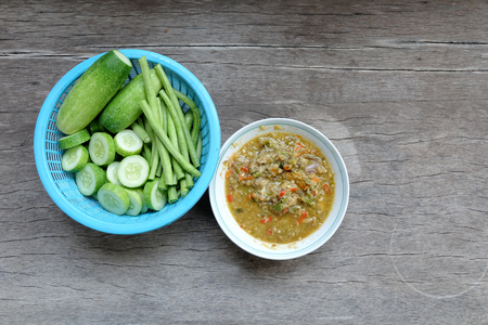 long bean: Fresh cucumber and long bean in the blue plastic basket with homemade chili paste on timber table