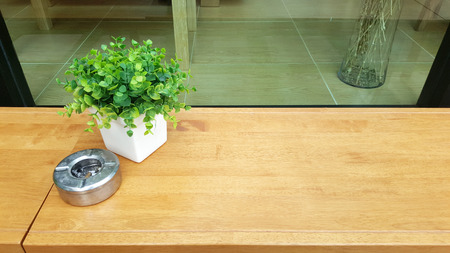 Syntactic decoration plants with ash tray on timber bench at smoking area