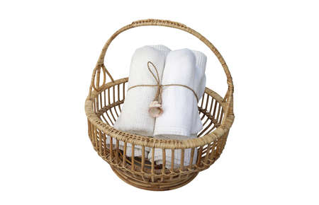 string together: Rolls of white color towel tight together by linen string with sea shell in the woven basket isolated