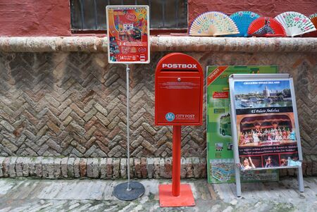 postbox: Seville, Spain - 8 December,2015 : Red postbox and tourist advertisment at souvenir shop on 8 December 2015 in Seville, Spain