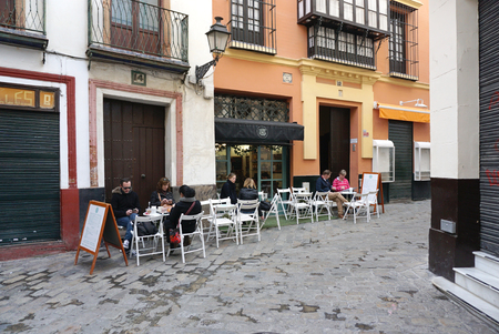 restuarant: Seville, Spain - 8 December,2015 : People having breakfast at the restuarant in the beautiful old building of Santa Cruz village on 8 December 2015 in Seville, Spain Editorial