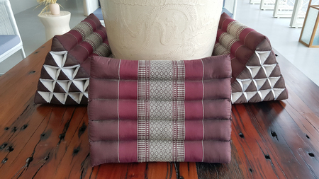 daybed: traditional Thai triangle pillow on the timber bench