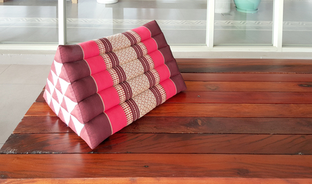 timber bench seat: traditional Thai triangle pillow on the timber bench