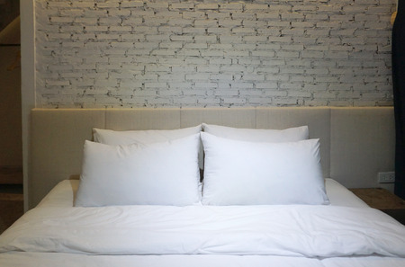 lighting background: Bedroom with White pillow and bedsheet and white brick background with focus lighting in the middle