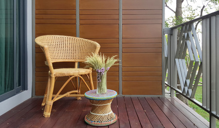 cane chair: wicker chair on the balcony outdoor with flower vase Stock Photo