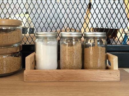 malla metalica: botellas de azúcar en la bandeja de madera con fondo de malla metálica