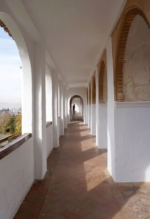 tile flooring: white arch corridor with terracotta tile flooring