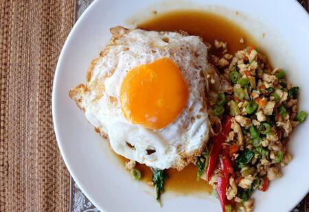 huevos estrellados: albahaca pollo y los huevos fritos de arroz blanco en la placa blanca Foto de archivo