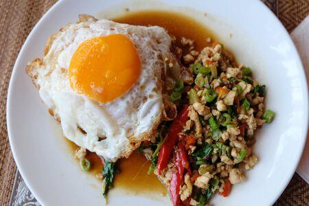 huevos estrellados: Basil pollo y huevos fritos con arroz en la placa blanca Foto de archivo